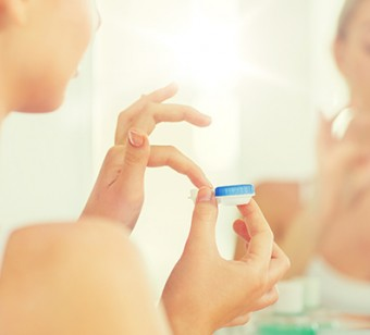 beauty, vision, eyesight, ophthalmology and people concept - close up of young woman applying contact lenses at mirror in home bathroom
