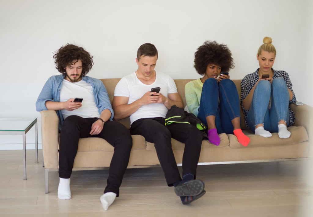 multiethnic group of young people sitting on a sofa at home,staring at smartphone, being antisocial, smartphone addiction