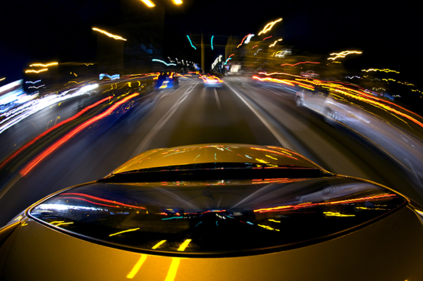 A car, surrounded by blurred other cars due to the high speed, driving in a busy down town area with lots of lights, traffic and traffic lights